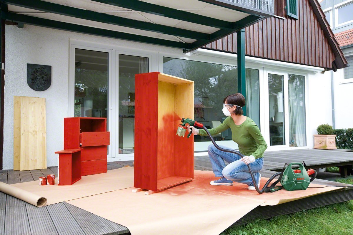 Woman painting furniture outside with bosch sprayer image