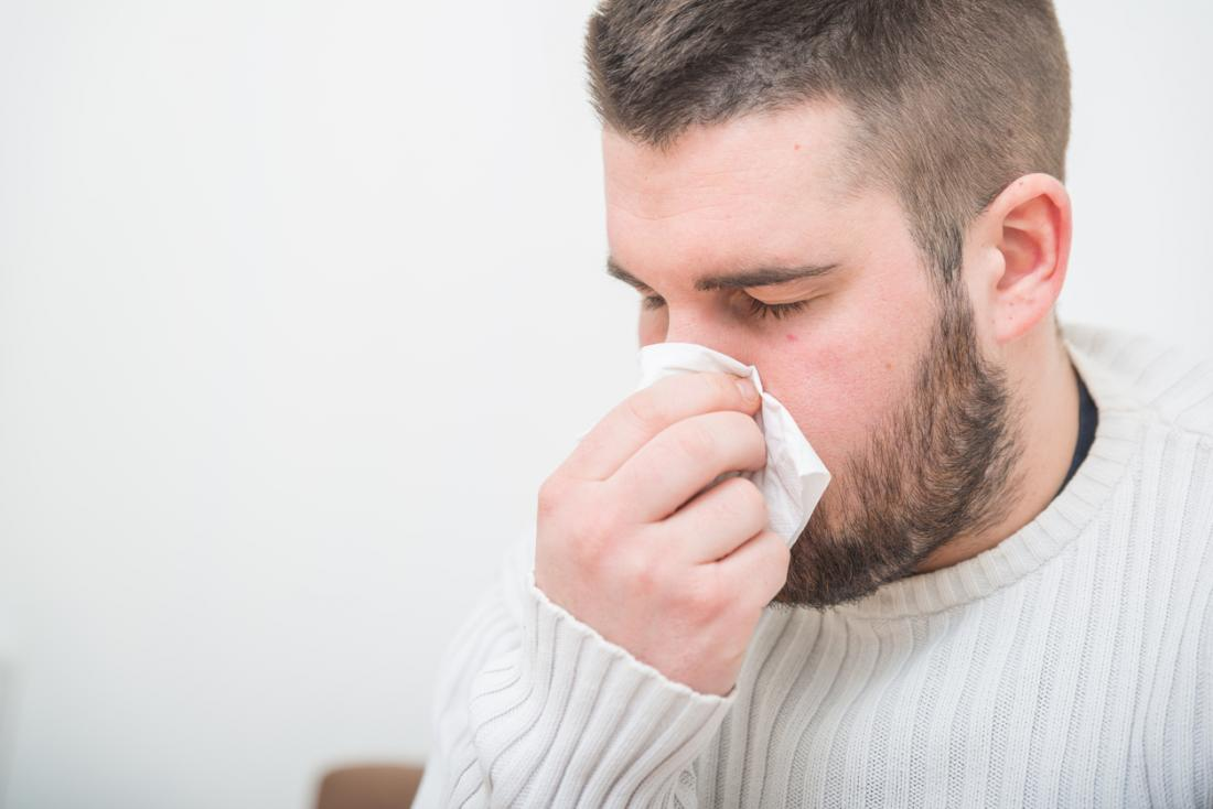 man gently blowing his nose because of flu or cold image